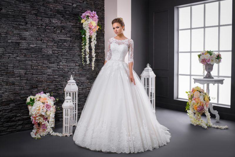 Торжественное свадебное платье с округлым декольте и изящными тонкими рукавами.