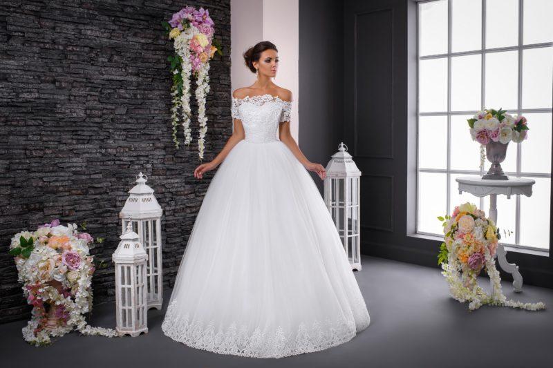Пышное свадебное платье с коротким рукавом из кружева и портретным вырезом.