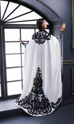 Длинное вечернее платье белого цвета, украшенное черными аппликациями.