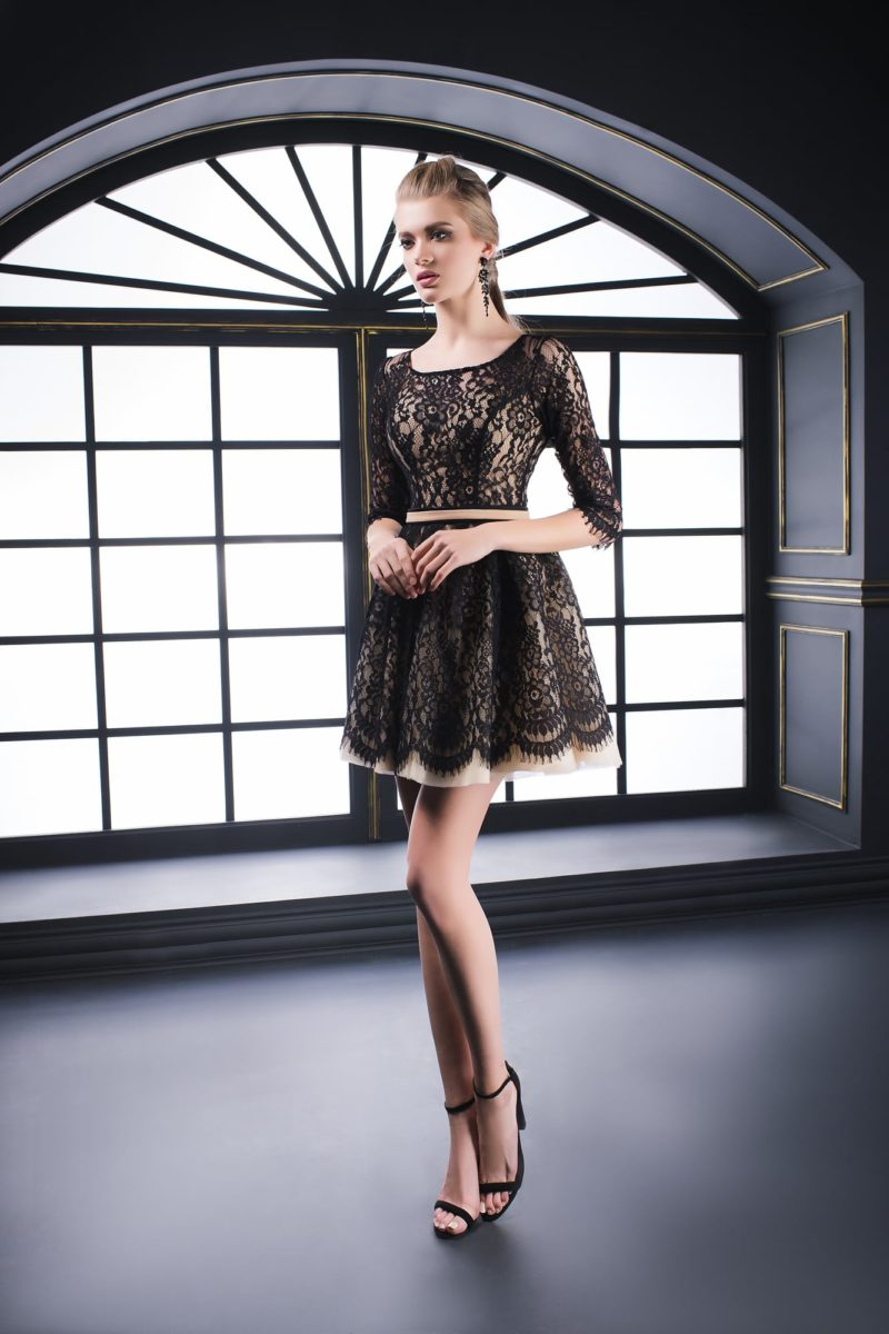 Короткое вечернее платье с бежевой подкладкой под слоем плотного черного кружева.