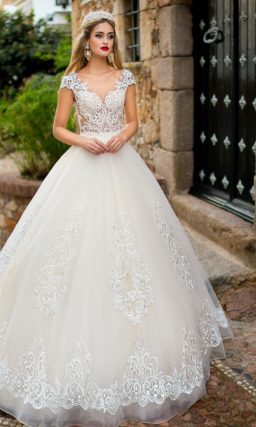 Свадебное платье с пышной юбкой и прозрачным верхом, декорированное крупным кружевом.