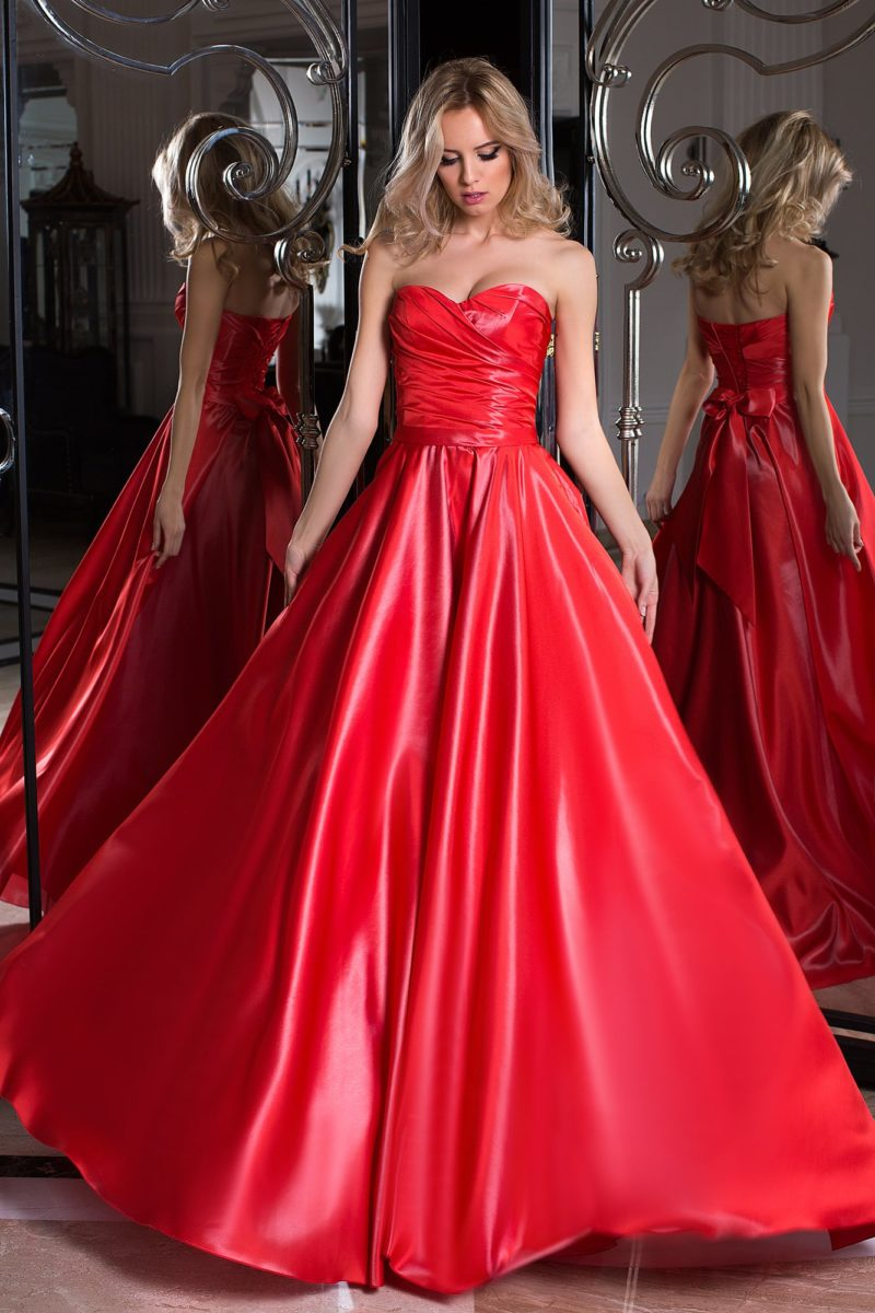 Пышное вечернее платье из роскошной алой ткани, с открытым вырезом.