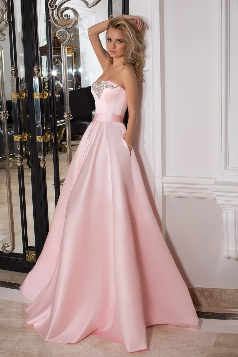 Глянцевое розовое вечернее платье пышного кроя со скрытыми карманами.