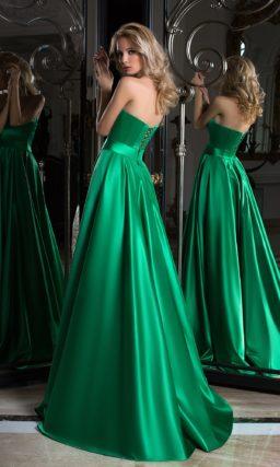 Изумрудное вечернее платье с золотистым декором и вырезом на спинке.