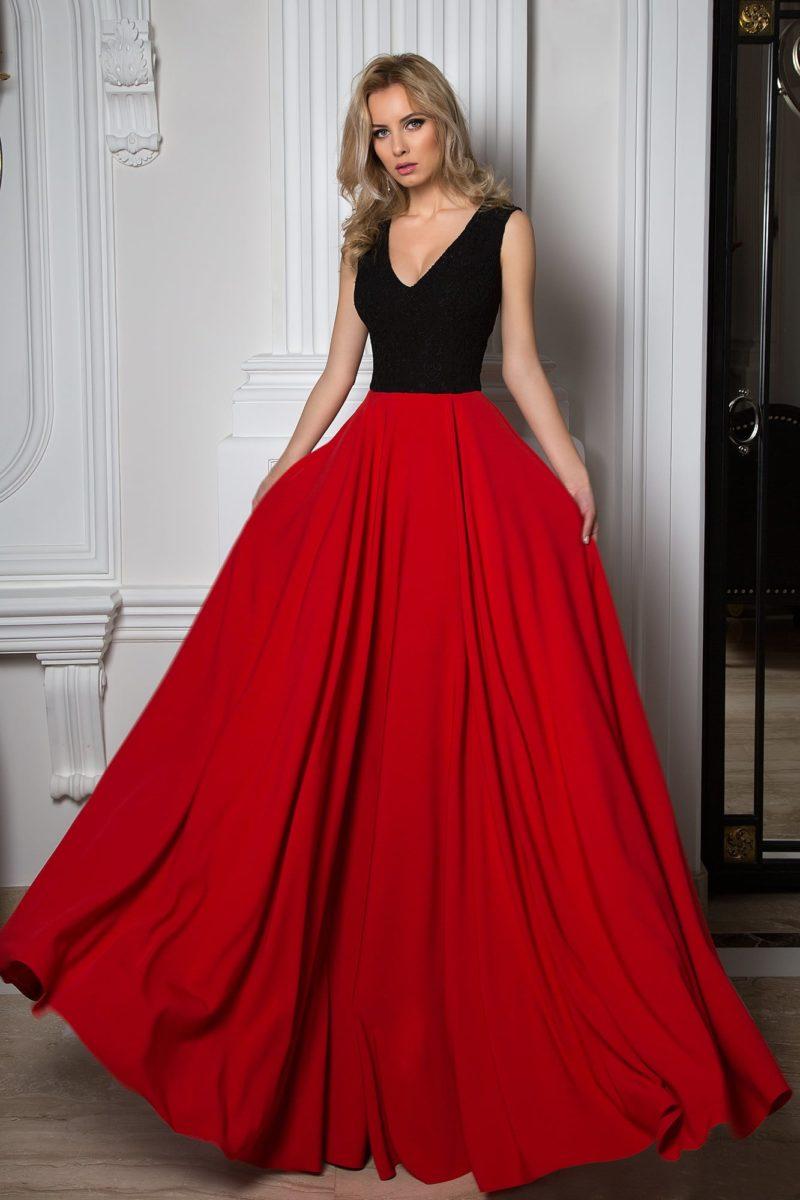 Вечернее платье с черным верхом с V-образным вырезом и красной юбкой.