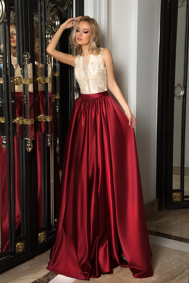 Стильное вечернее платье с темно-красной юбкой и белым верхом, покрытым вышивкой.