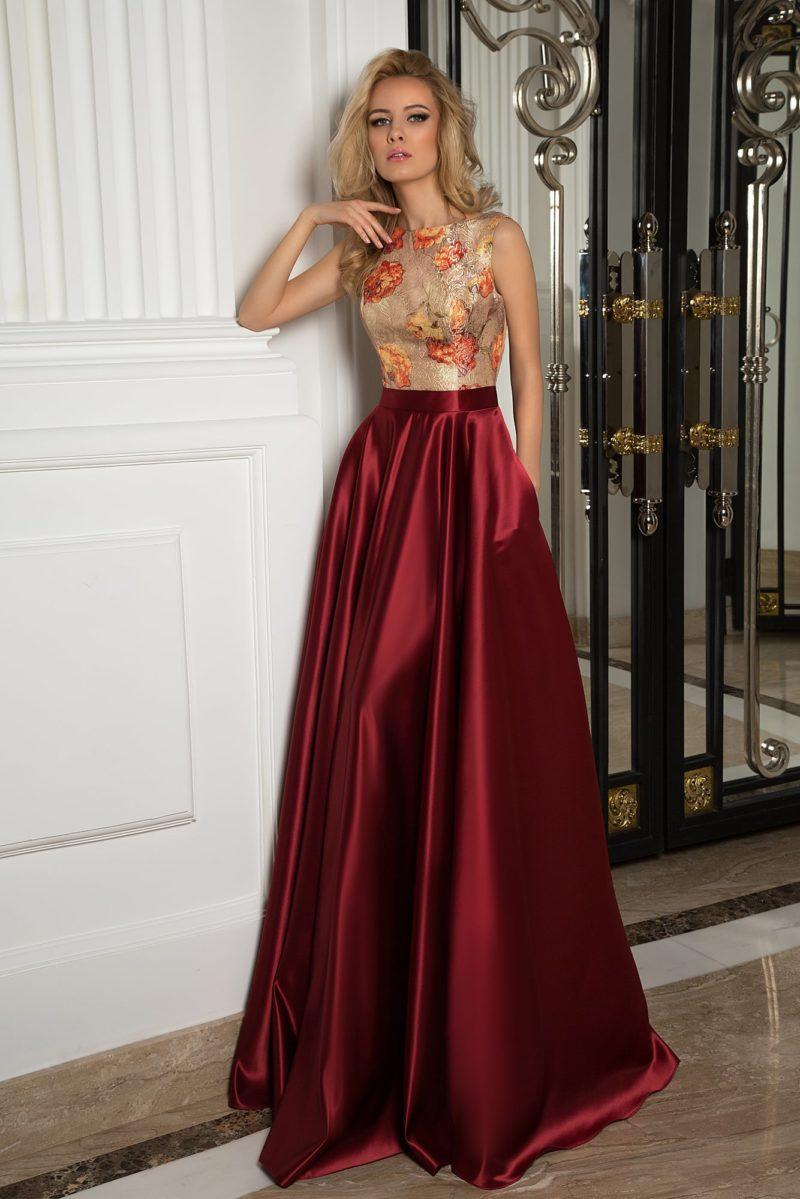 Пышное вечернее платье с бордовой юбкой и закрытым верхом с цветочным узором.