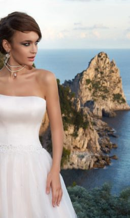 Пышное свадебное платье оттенка слоновой кости с открытым декольте и вышивкой по юбке.
