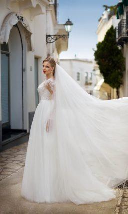 Классическое свадебное платье пышного кроя с длинным полупрозрачным рукавом и декором из кружева.