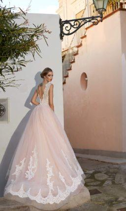 Свадебное платье розового цвета, декорированное белым кружевом по низу многослойной юбки.