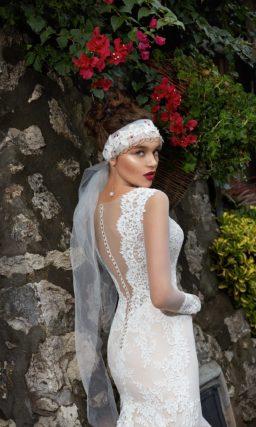 Закрытое свадебное платье цвета слоновой кости с юбкой кроя «трапеция» и кружевным декором.
