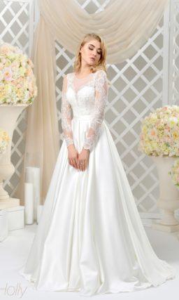 Закрытое свадебное платье с полупрозрачным рукавом и роскошной юбкой из атласа.