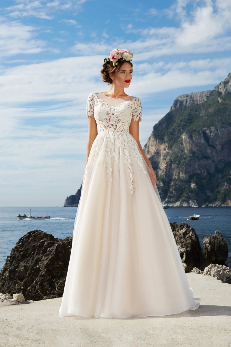 Фактурное свадебное платье пышного кроя цвета слоновой кости с коротким рукавом из кружева.