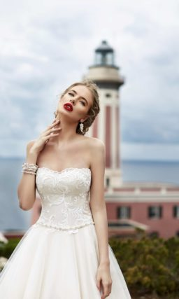 Пышное свадебное платье с открытым бежевым корсетом, деликатно оформленным вышивкой.