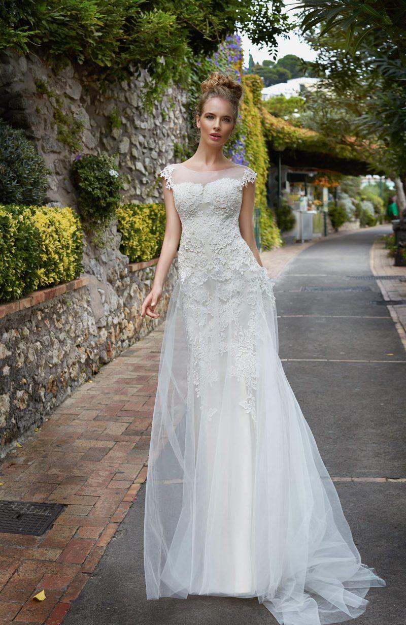 Прямое свадебное платье с закрытым лифом, кружевной отделкой и тонкой верхней юбкой.