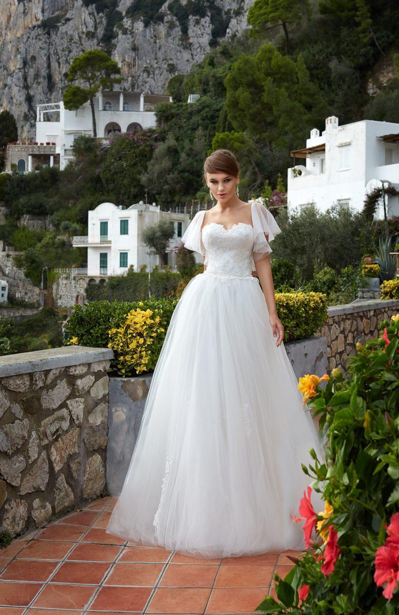 Пышное свадебное платье с кружевной отделкой открытого лифа и объемными рукавами.