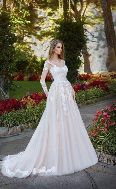 Роскошное свадебное платье с длинным прозрачным рукавом, оформленное плотными кружевными аппликациями.