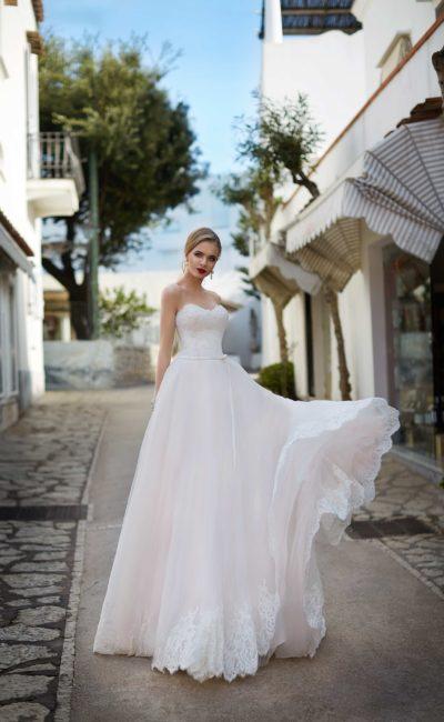 Романтичное свадебное платье с пышной юбкой со шлейфом и соблазнительным открытым корсетом.