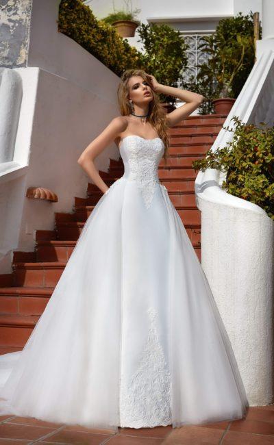 Пышное свадебное платье с длинным шлейфом и кружевной отделкой по корсету и низу подола.