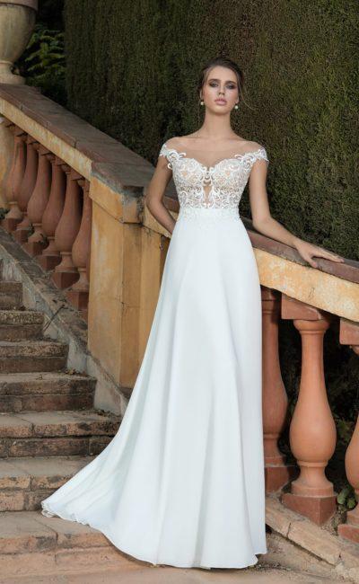 Сдержанное свадебное платье с полупрозрачным корсетом и элегантным шлейфом.