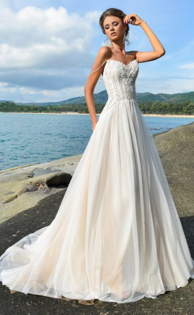 Романтичное свадебное платье с розовой подкладкой на юбке и кружевным лифом.