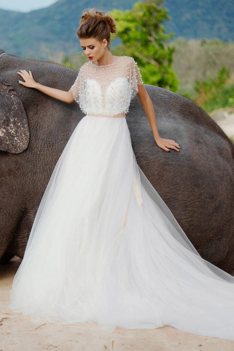 Пышное свадебное платье с необычным верхом с коротким полупрозрачным рукавом.