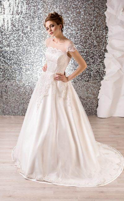 Свадебное платье с пышной атласной юбкой и полупрозрачной вставкой над лифом.