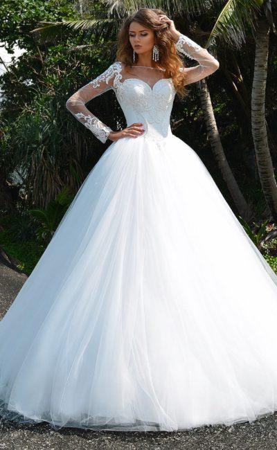 Пышное свадебное платье с отделкой кружевом и длинными прозрачными рукавами.