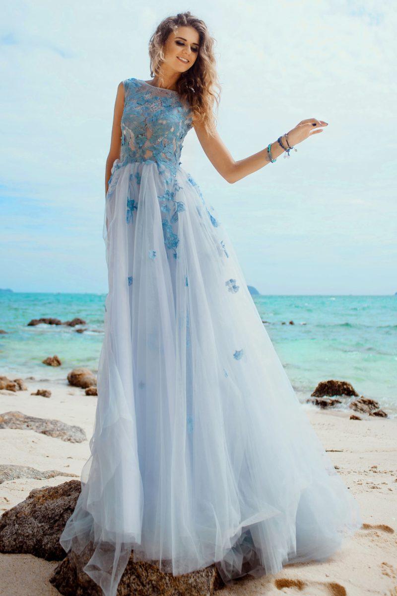 Необычное свадебное платье с многослойным подолом и голубыми аппликациями.
