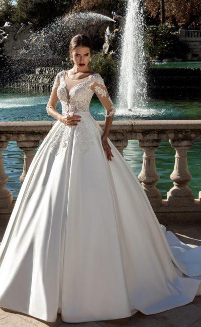 Атласное свадебное платье пышного кроя с фактурными аппликациями и вышивкой.