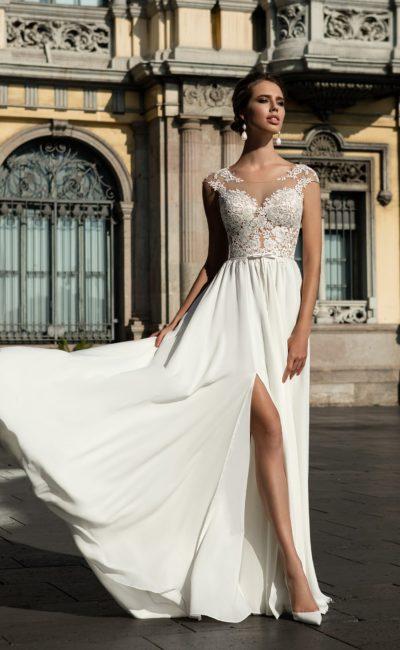 Прямое свадебное платье со стильным разрезом на юбке и кружевным верхом.