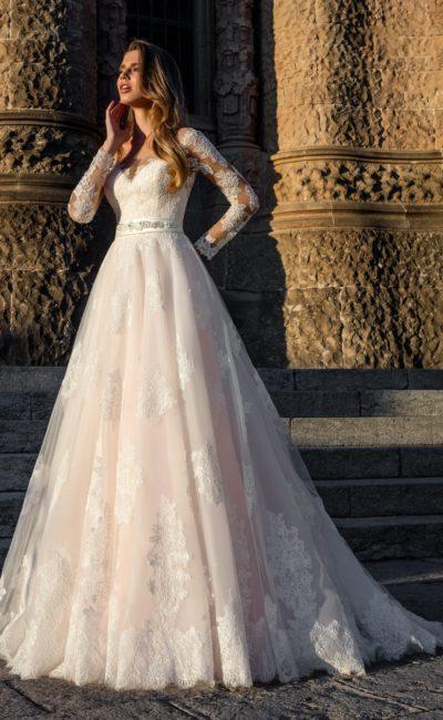 Пышное свадебное платье с персиковой подкладкой на юбке и кружевным рукавом.