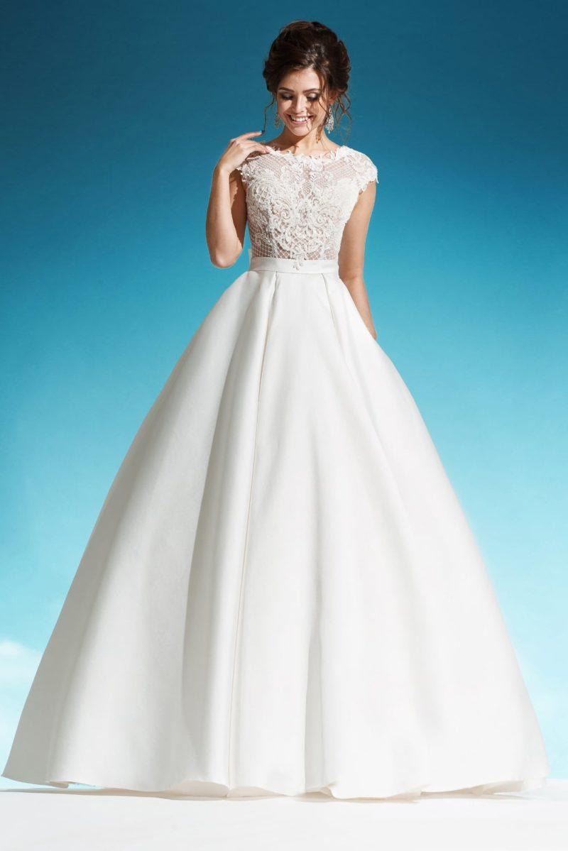 Торжественное свадебное платье с пышным подолом и объемным бантом на спинке.