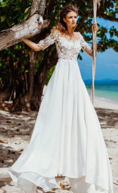 Свадебное платье со стильной шифоновой юбкой и закрытым верхом с аппликациями.