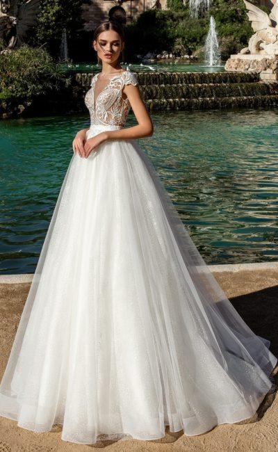 Свадебное платье с многослойной юбкой и глубоким V-образным вырезом на спинке.