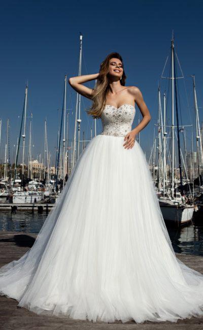 Романтичное свадебное платье с пышным низом и верхом, украшенным стразами.