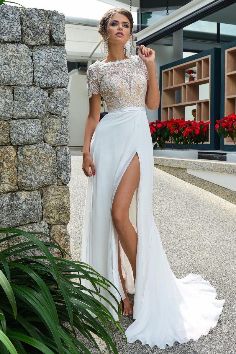 Прямое свадебное платье с разрезом по подолу и бежевым корсетом, покрытым кружевом.