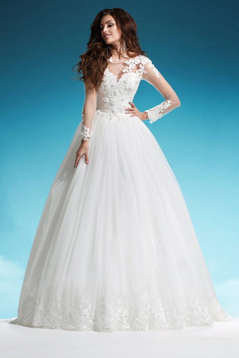 Пышное свадебное платье с фактурными аппликациями и длинным тонким рукавом.