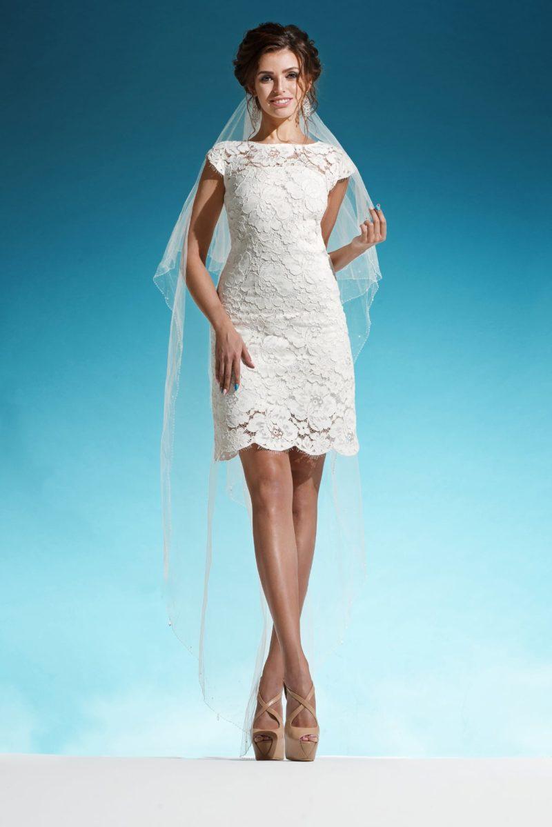 Короткое свадебное платье, покрытое кружевом, с округлым вырезом и фигурным подолом.