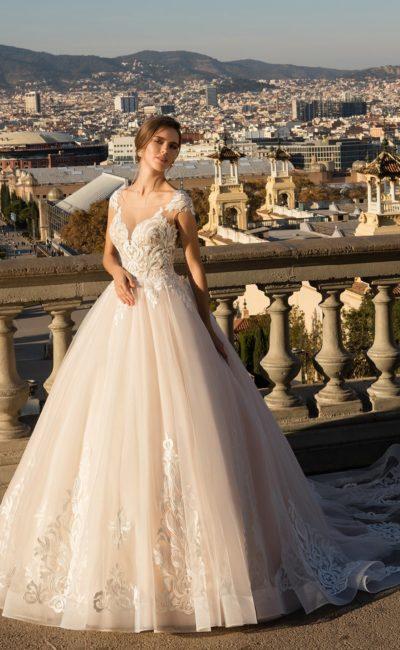 Розовое свадебное платье пышного кроя с крупным декором и тонким шлейфом сзади.