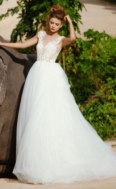 Шикарное свадебное платье с полупрозрачным верхом, покрытым кружевной отделкой.