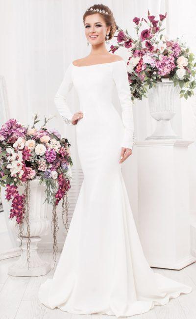 Атласное свадебное платье с портретным декольте и стразами на длинных рукавах.