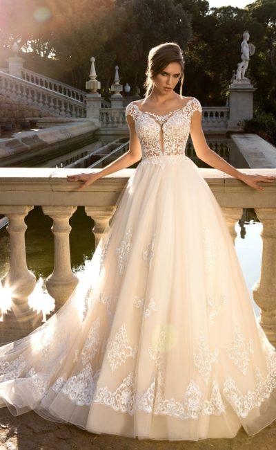 Бежевое свадебное платье пышного кроя с полупрозрачным верхом, покрытым кружевом.