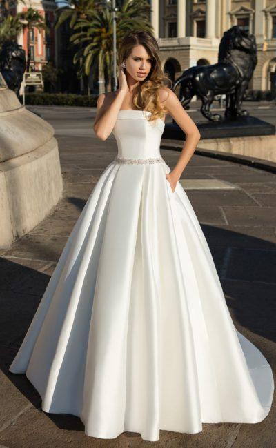 Атласное свадебное платье с глубоким вырезом сзади и скрытыми карманами.