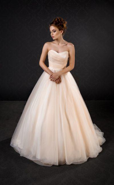 Лаконичное свадебное платье бежевого цвета с многослойной пышной юбкой со шлейфом.