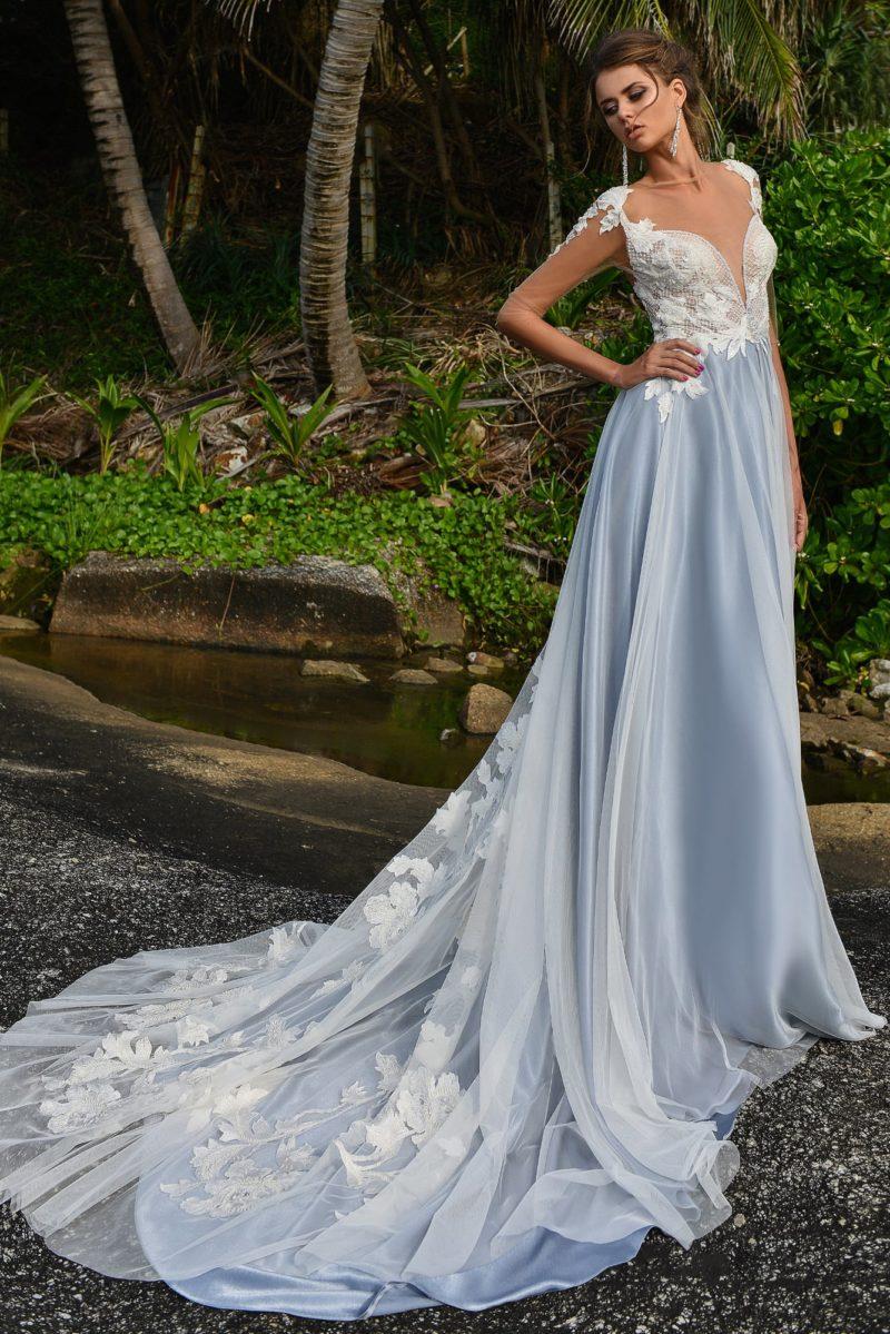 Голубое свадебное платье с пышным низом и полупрозрачными длинными рукавами.