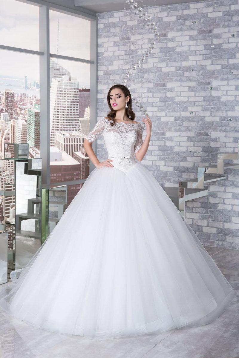 Невероятно пышное свадебное платье с длинным рукавом из кружевной ткани.