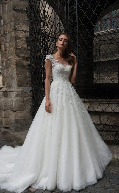 Свадебное платье А-силуэта с объемной отделкой, коротким рукавом и длинным шлейфом.
