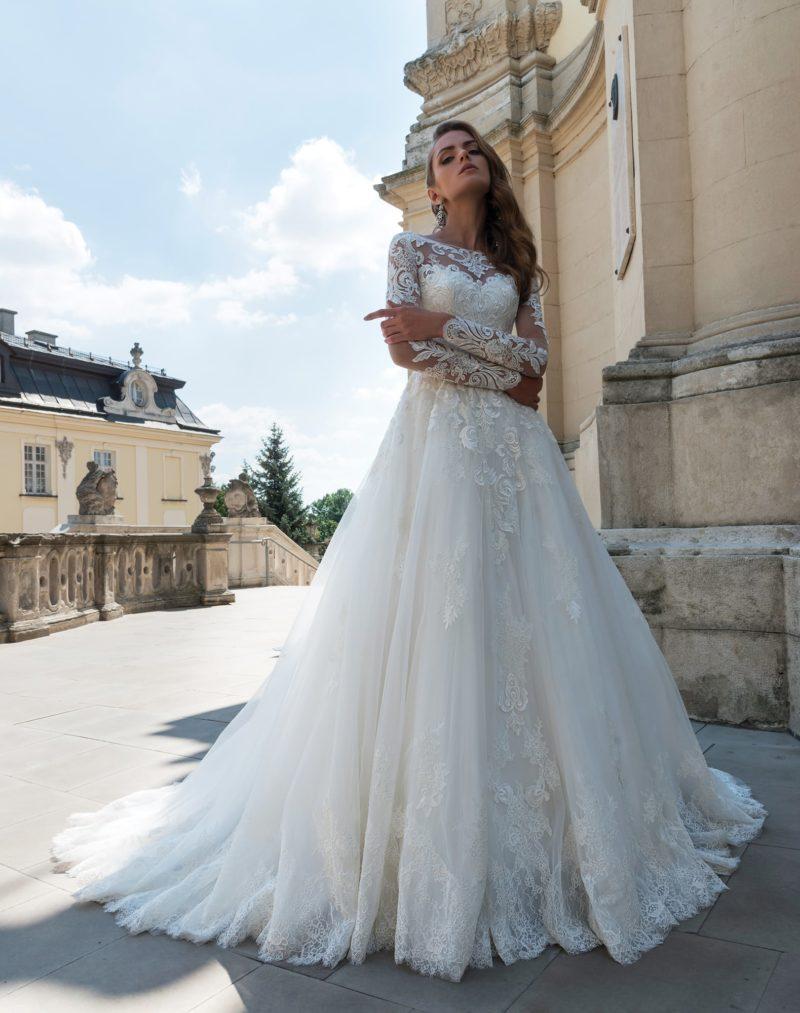 Великолепное свадебное платье с длинным полупрозрачным рукавом и кружевным декором.