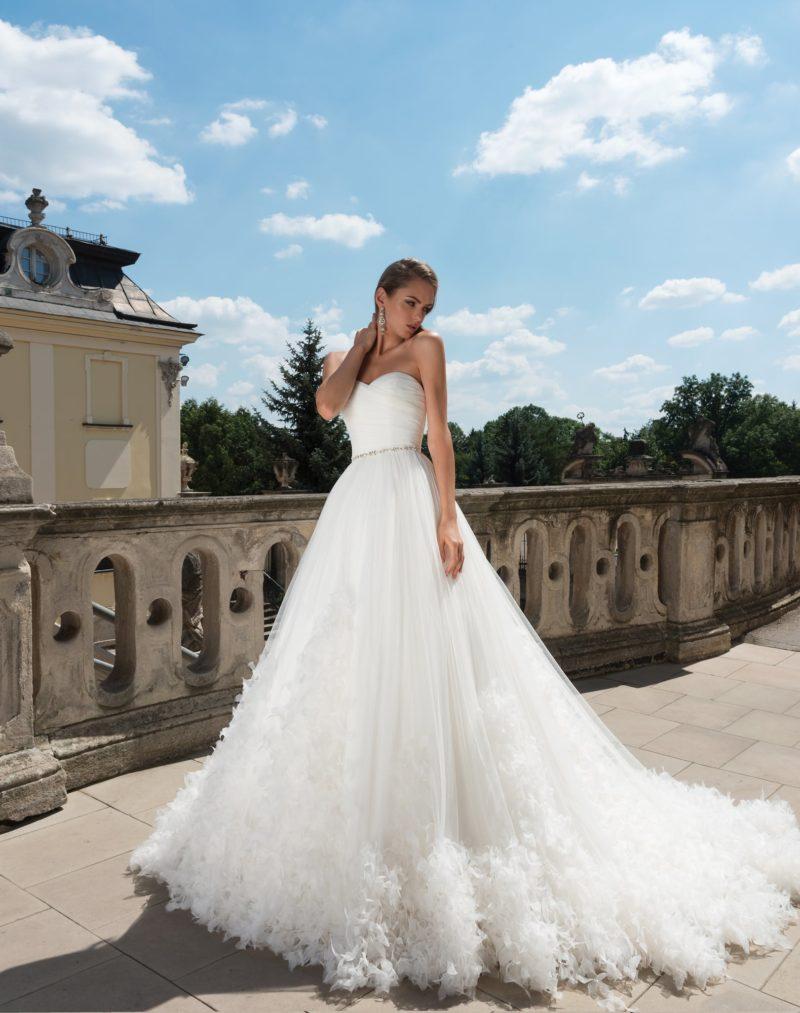 Открытое свадебное платье с лифом в форме сердца и кокетливым декором низа подола.